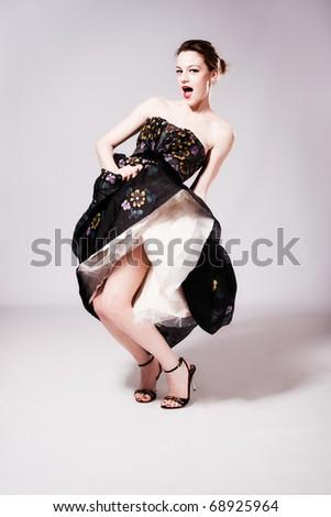happy young woman dancing in fancy dress, studio shot, full body shot - stock photo