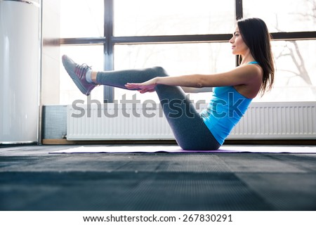 Happy young woman doing exercise on yoga mat at gym - stock photo