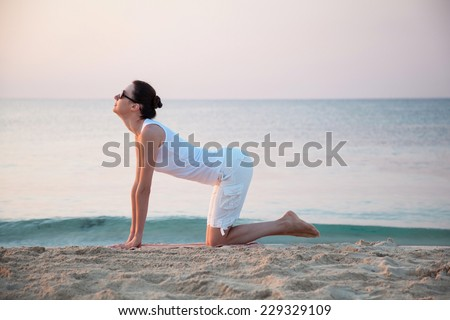 Happy young woman doing exercises sitting on sea coast at dawn