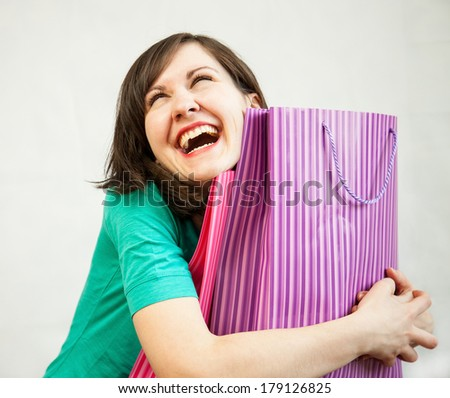 Happy young woman doing shopping, neutral background - stock photo