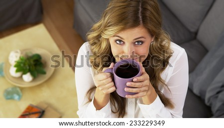 Happy young woman drinking coffee in living room - stock photo