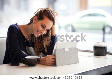 Happy young woman drinking coffee / tea and using tablet computer in a coffee shop - stock photo