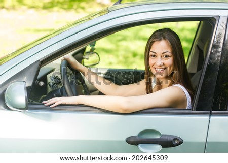 Happy young woman driving a car.