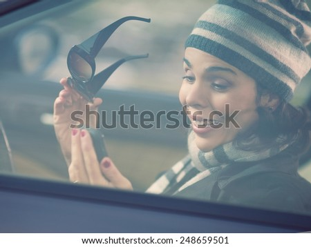 Happy young woman driving a car and using mobile phone - stock photo