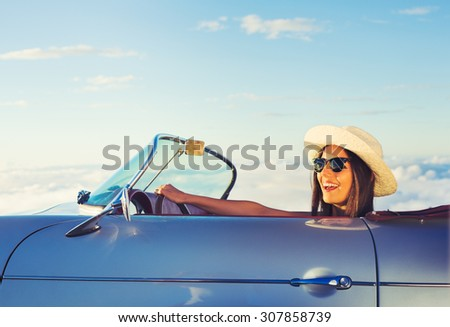 Happy Young Woman Driving in Classic Vintage Sports Car - stock photo