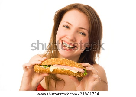 happy young woman eating a hot-dog isolated against white background