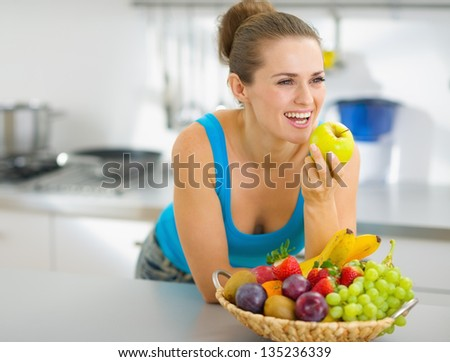 Happy young woman eating apple in modern kitchen - stock photo