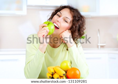 Happy Young Woman Eating Apple on Kitchen. Diet. Dieting concept. Healthy food