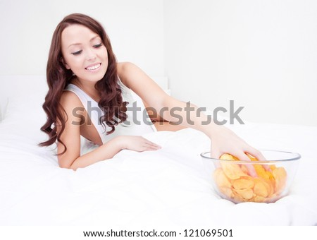 happy young woman eating potato chips in bed at home - stock photo