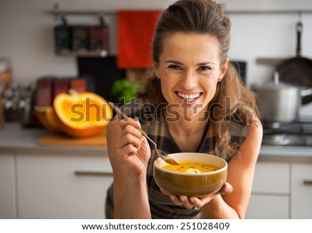 Happy young woman eating pumpkin soup in kitchen - stock photo