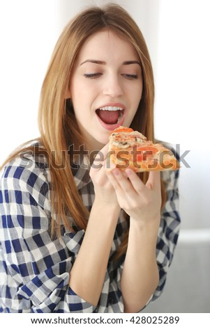 Happy young woman eating slice of hot pizza at home
