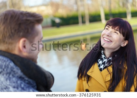 Happy young woman enjoying a day outdoors with her husband looking up into the air with a vivacious smile as they stand beside a canal - stock photo