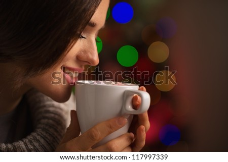 Happy young woman enjoying cup of hot beverage in front of Christmas lights - stock photo
