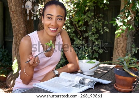 happy young woman enjoying healthy salad bowl reading magazine outdoors