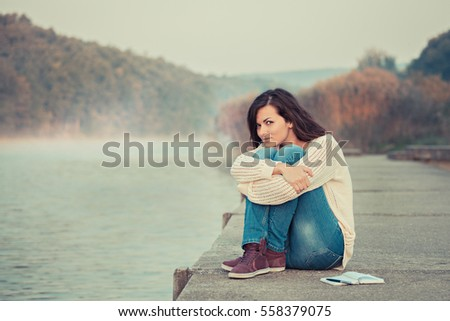 Happy young woman enjoying nature. Sitting by the lake. Chilly morning.