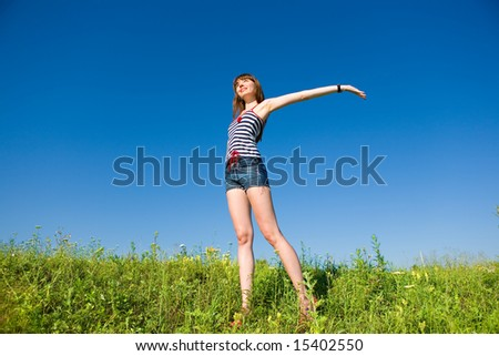 Happy young woman enjoying summer. Against the backdrop of blue sky.