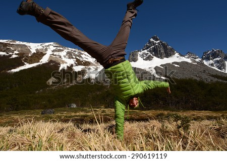 Happy young woman enjoys beautiful view into high mountains, Andes, South America - stock photo