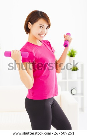 happy young woman exercising with dumbbells in living room - stock photo