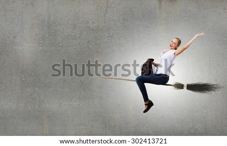Happy young woman flying in sky on broom - stock photo