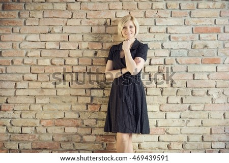 Happy young woman front of brick wall, smiling.
