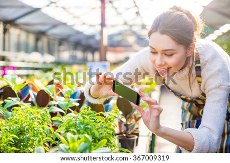Happy young woman gardener taking picture of green plants and flowers with smartphone in greenhouse - stock photo
