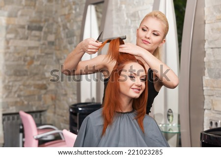 Happy young woman getting a new haircut. Beautiful young hairdresser giving new haircut to female customer at parlor  - stock photo