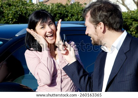 Happy young woman getting a special surprise new car from boyfriend - stock photo