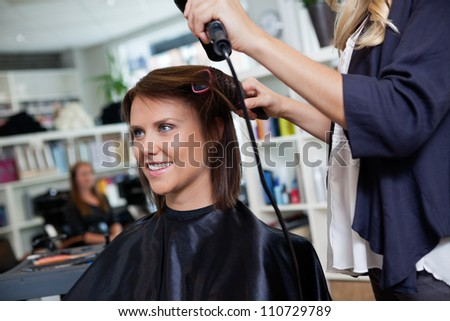 Happy young woman getting her hair set by beautician after the new haircut