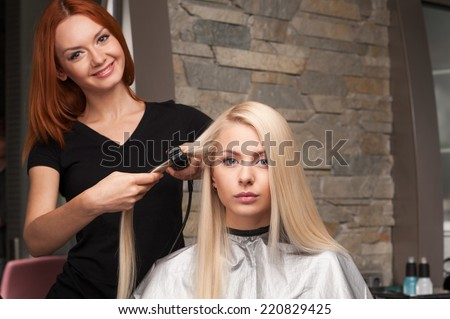 Happy young woman getting new haircut by hairdresser at parlor. redhead hairdresser straightening client's hair in beauty salon - stock photo