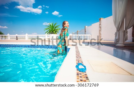 Happy young woman getting out of a  swimming pool. The woman is wearing a dress.  - stock photo