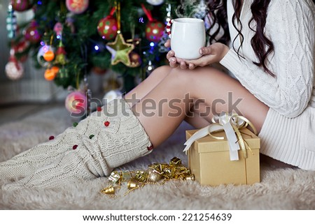Happy young woman giving christmas present and cup - stock photo