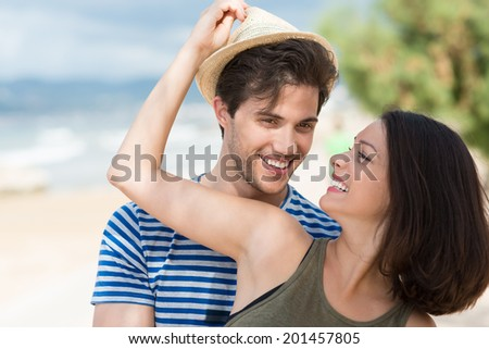 Happy young woman giving her husband a hat placing her stylish straw sunhat on his head with a smile as they stand together on a tropical beach - stock photo