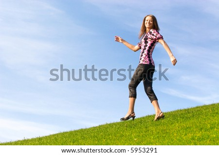 Happy young woman goes down from a hill.