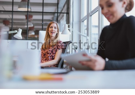 Happy young woman having a friendly chat with her female colleague while at work - stock photo