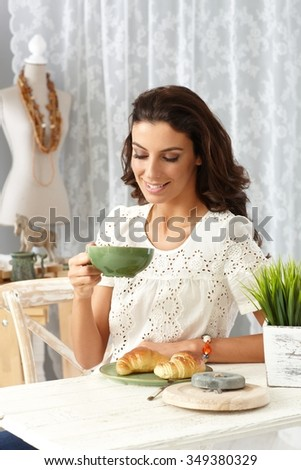 Happy young woman having breakfast at home, smiling, drinking tea. - stock photo