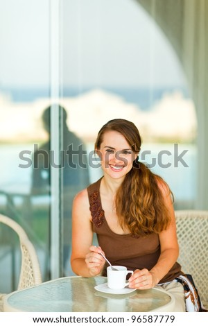 Happy young woman having cup of coffee at terrace