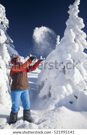 Happy young woman having fun in the snow