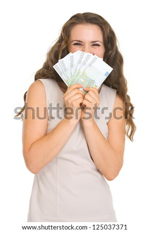 Happy young woman hiding behind fan of euros - stock photo