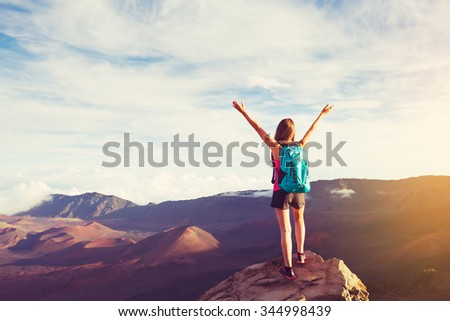Happy Young Woman Hiker With Open Arms Raised at Sunset on Mountain Peak - stock photo