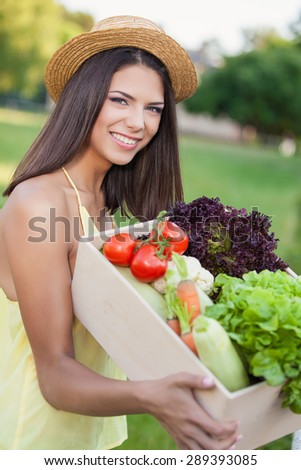 Happy young woman holding a crate of freshly harvested vegetables