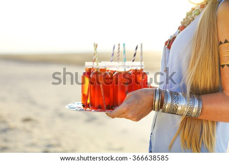 Happy young woman holding a dish with a drinks at summer beach party