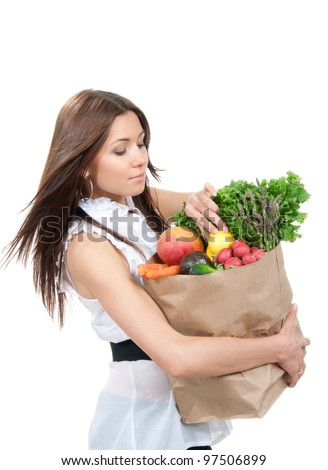 Happy young woman holding a grocery shopping bag full of groceries, mango, salad, asparagus, radish, avocado, lemon, carrots on white background - stock photo