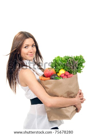 Happy young woman holding a paper shopping bag full of groceries, mango, salad, asparagus, radish, avocado, lemon, carrots on white background - stock photo