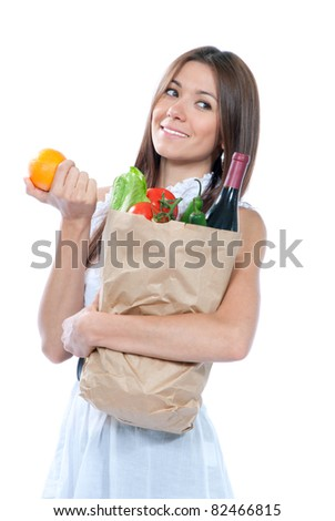 Happy young woman holding a paper shopping bag full of groceries, pepper, salad, asparagus, bottle of wine, tomatoes, orange, carrots on white background