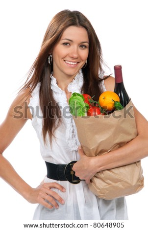 Happy young woman holding a paper shopping bag full of groceries salad, green pepper, tomatoes, orange, bottle of wine isolated on white background - stock photo