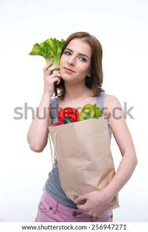 Happy young woman holding a shopping bag full of groceries - stock photo