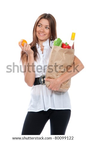 Happy young woman holding a shopping bag full of groceries, fresh salad, red pepper, bottle of wine and orange in hand isolated on white background - stock photo