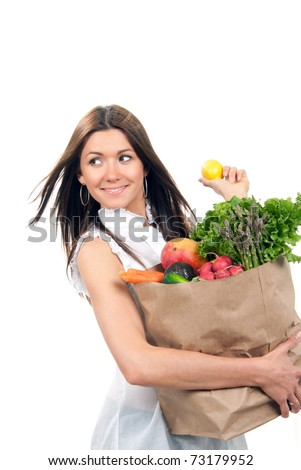 Happy young woman holding a shopping bag full of groceries, mango, salad, asparagus, radish, avocado, lemon, carrots on white background - stock photo
