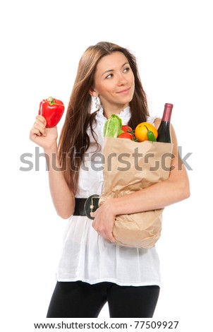 Happy young woman holding a shopping bag full of groceries, mango, salad, red pepper, radish, tomato, orange, bottle of wine on white background - stock photo