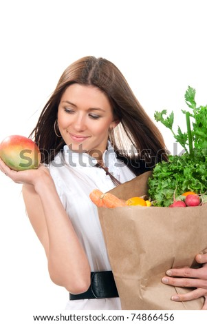 Happy young woman holding a shopping bag full of vegetarian groceries, mango in hand, salad, asparagus, radish, avocado, lemon, carrots, oranges isolated on white background